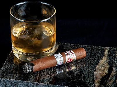 A glass of whisky and ice next to a large, lit cigar
