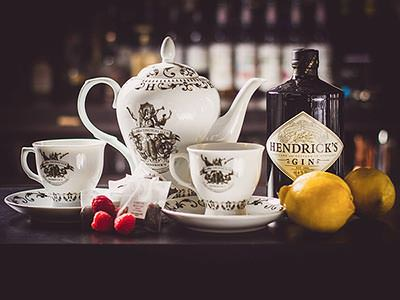 Close up of a vintage tea set with a white teapot and two cups, placed alongside a bottle of Hendricks gin, beeries and a lemon