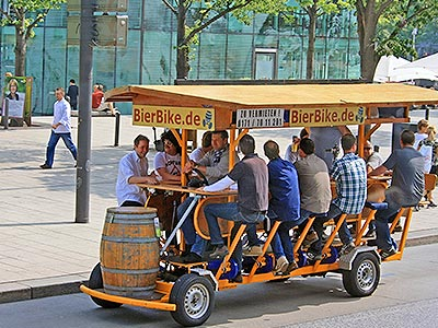 People pedalling on a beer bike on a road during the day