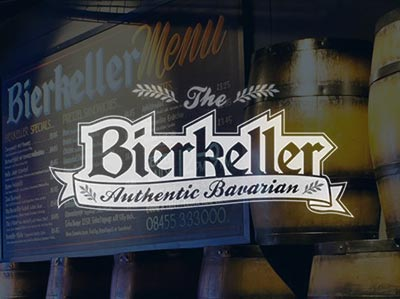 The Bierkeller menu mounted on the wall, surrounded by wooden kegs