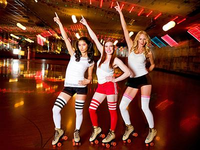 Three women in retro roller disco costumes and skates, pointing in the air and posing