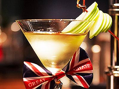 A cocktail with sliced apples on the rim, and a Great British flag ribbon on the stem