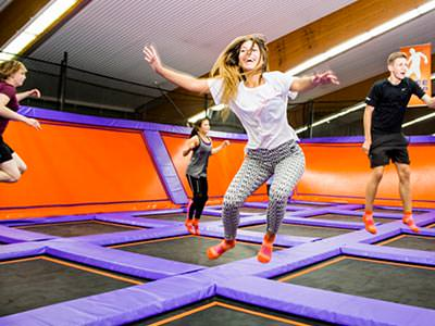 People jumping on trampolines in an indoor centre