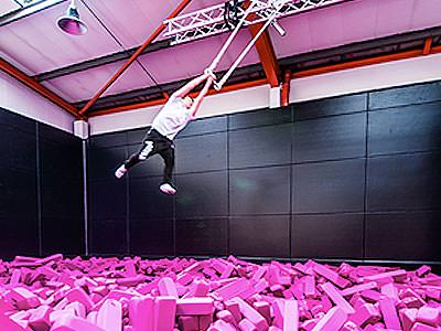 A man swinging above pink foam blocks