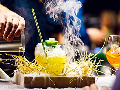 A cocktail on a wooden board, surrounded by twigs and smoke