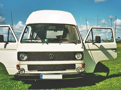 A white camper van parked up, with two open doors