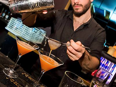 A male bartender pouring out orange cocktails through a sieve
