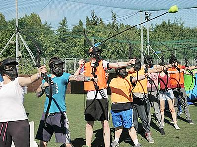 A row of people aiming and firing battlezone archery arrows