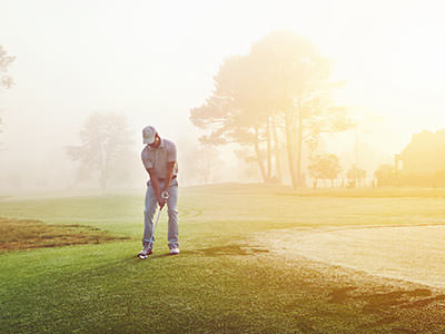 A man playing golf, with a misty sunrise in the background
