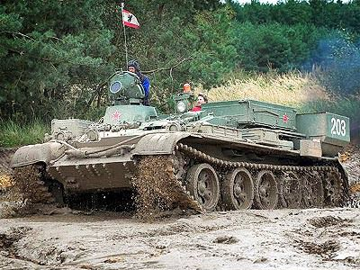 An armoured vehicle driving through wet mud