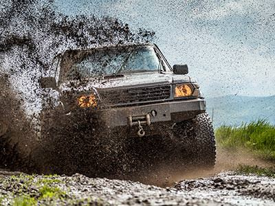 A 4x4 vehicle driving through the mud outdoors