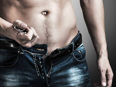 The groin and stomach of a topless man wearing unbuttoned jeans