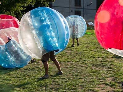 People playing in pink and blue zorbs on a pitch