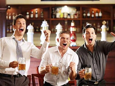 Three men in a bar, holding pints and celebrating