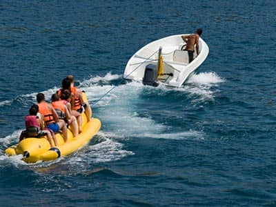A line of people sat on a banana boat, being pulled by a white boat in the sea