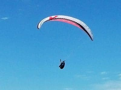 Someone parasailing against a blue sky