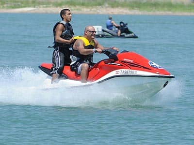 Two men on a Jet Ski, with another Jet Ski in the background