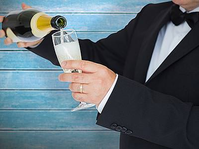 A man wearing black tie filling a flute glass from a bottle of champagne