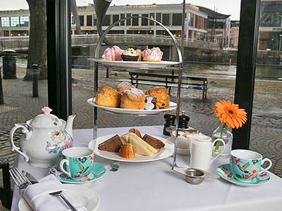 Afternoon tea laid out on a table in front of a glass window