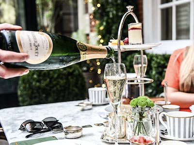 A hand pouring out a bottle of champagne into a flute, with afternoon tea in the background