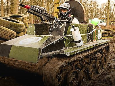A man sat in a mini tank, equipped with a paintball gun, in the woods