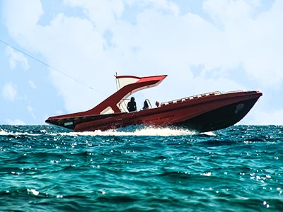 A speedboat on the ocean with blue sky and clouds in the background