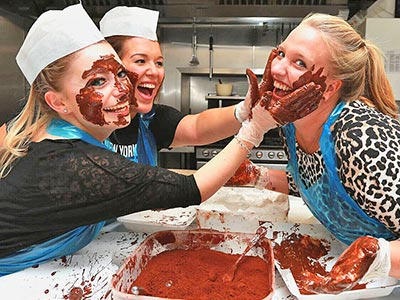 Two chocolate-covered women rubbing chocolate on a woman's face