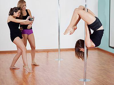 A girl pole dancing while two girls watch