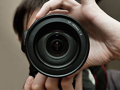 A person holding a lens of a camera up to the foreground of the image
