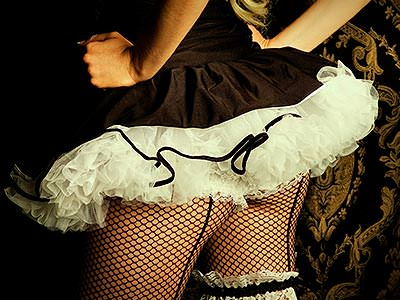 A close up of a woman's bum in suspenders and a tutu
