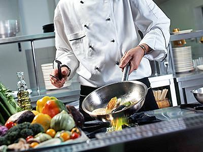 A chef putting ingredients into a pan