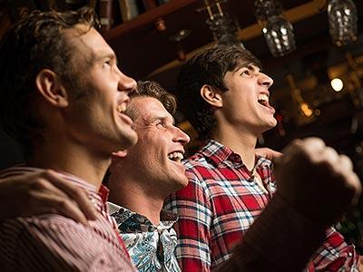 Three men shouting in a bar