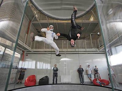An indoor skydiving tube with two people floating inside
