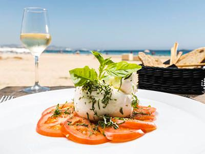 A mozzarella and tomato salad on a white plate, with a glass of wine and beach in the background