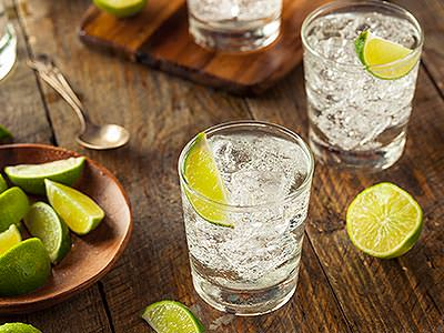 Two gin and tonics with limes in, on a wooden bench