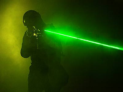 Silhouette of a man shooting a green laser from a laser gun, to a smoky black backdrop