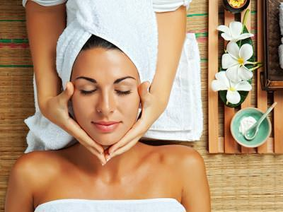A woman receiving a face massage on a table, with a spa tray next to the head