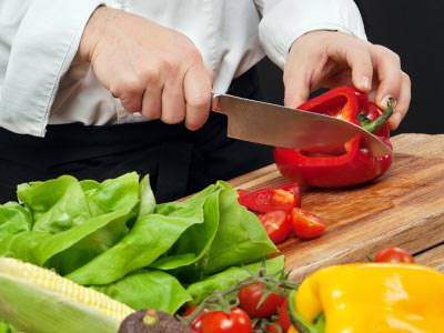 A woman's hand chopping a red pepper, with lettuce and yellow peppers in the corner