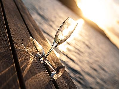 Two champagne flutes on a table, with the sun setting over the sea in the background