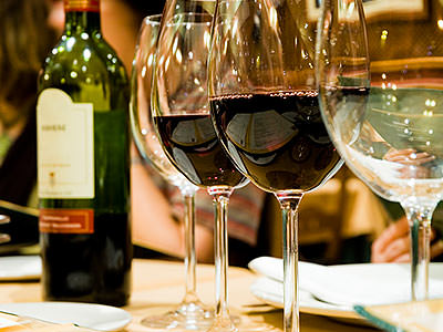 Two glasses of red wine, next to two empty wine glasses and a bottle of red