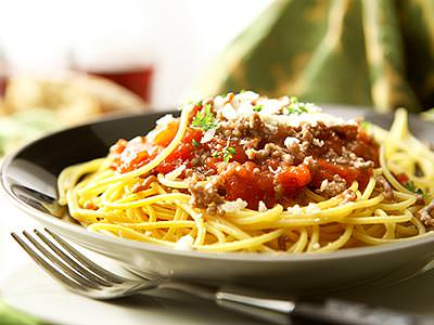 A bowl of spaghetti with tomato and mince on the top