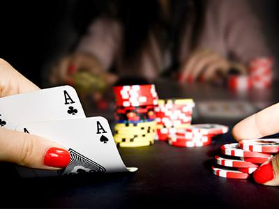 A person playing poker, with two aces in their hand
