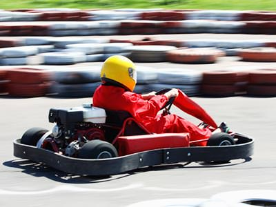 A person driving a kart outdoors, in a yellow helmet and red overalls