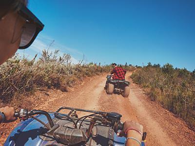 Two people quad biking down a dirt path