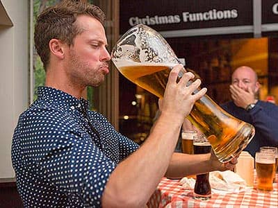 A man drinking beer from a massive pint glass, with a man looking on in the background