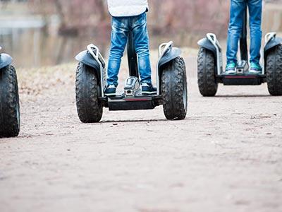 Three men's legs driving Segways on a path