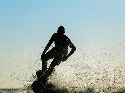 Silhouette of a man flyboarding above the sea