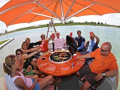 A group of people sat around a grill boat, on a river