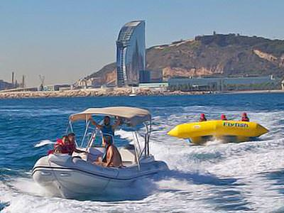 A speed boat and a banana boat on the sea, with Barcelona in the background