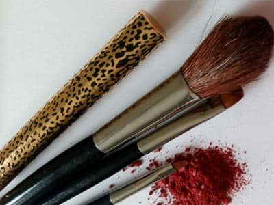 Make up brushes next to red powder on a table